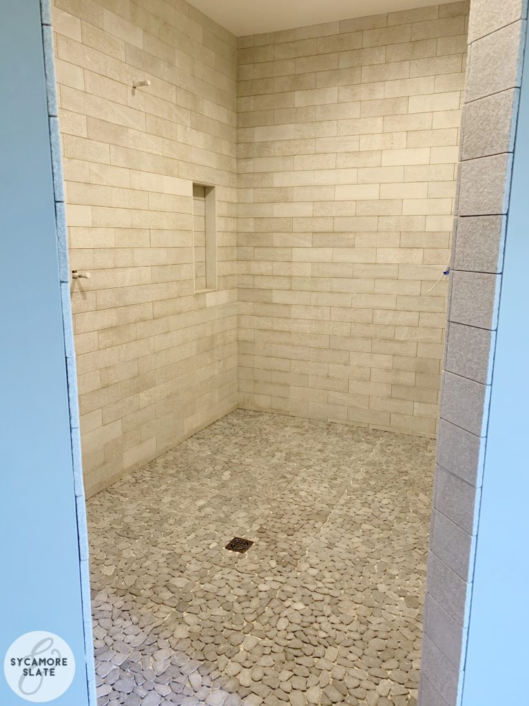 Master Bathroom Walk-in Shower with natural stone subway tile and flat pebble tile on floor