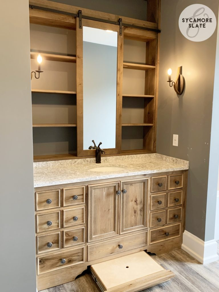 evie's vanity - sliding barn door mirror with open shelving behind it and a hidden drawer / stool combination