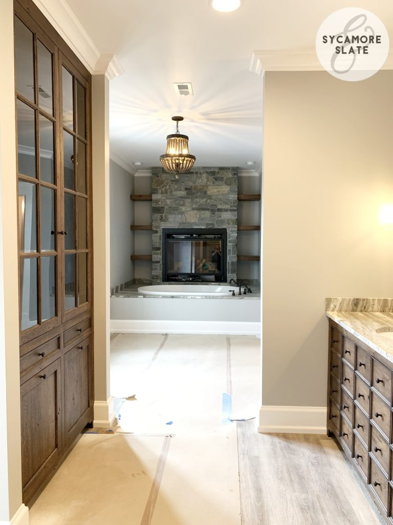 master en suite bathroom with vanity,built in linen cabinet, bathtub and fireplace shown